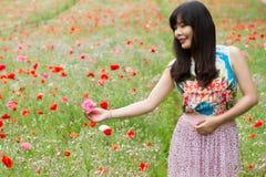 Mädchen spielt mit einer Blume auf dem Mohnblumengebiet lizenzfreie stockfotografie