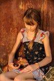 Mädchen spielt mit roten neugeborenen Schweinen der Duroczucht Das Konzept von mitfühlendem und von Interessieren für Tiere stockfoto