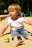 Mädchen spielt Sand auf einem Strand Lizenzfreies Stockbild