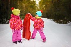Mädchen sprechen über das Rodeln im Wald Stockfotografie