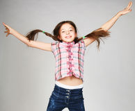Mädchen springt auf einen grauen Hintergrund Stockbild