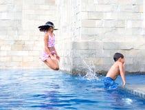 Mädchen springt in den Swimmingpool Stockfotografie