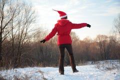 Mädchen springt in Holz im Winter von der Rückseite Lizenzfreies Stockfoto
