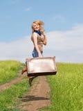 Mädchen springt mit einem Koffer Lizenzfreies Stockfoto