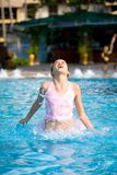 Mädchen springt von einem Swimmingpool heraus Stockbild