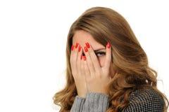 Mädchen starrt durch ihre Finger an Lizenzfreie Stockfotografie