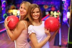 Mädchen stehen und halten Kugel im Bowlingspielklumpen Stockfotografie