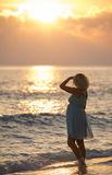 Mädchen steht auf dem maledivischen Strand und passt den Sonnenaufgang auf Stockbild