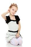 Mädchen steht auf ihren Knien und richtet ihr Armhaar gerade Lizenzfreies Stockbild