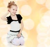 Mädchen steht auf ihren Knien und richtet ihr Armhaar gerade Stockfoto
