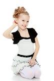 Mädchen steht auf ihren Knien und richtet ihr Armhaar gerade Lizenzfreie Stockfotografie