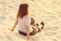 Mädchen steht das Sitzen auf dem Sand still Lizenzfreie Stockbilder