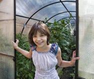 Mädchen steht an der Schwelle zu Gewächshäusern Lizenzfreie Stockfotografie