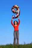 Mädchen steht in der Wiese und führt Abbildung von neun Lizenzfreie Stockfotografie