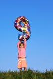 Mädchen steht in der Wiese und führt Abbildung von neun Lizenzfreies Stockfoto