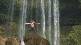 Mädchen steht in der Yogahaltung auf braunem Felsen am Wasserfall stock video