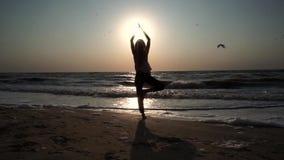 Mädchen steht in einer Yogahaltung, gegenüber von der Sonne bei Sonnenuntergang, auf dem Strand, auf dem Meer stock video