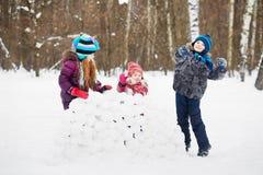 Mädchen steht hinter der Wand, die von den Schneeblöcken, Jungenwurfsschneeball hergestellt wird Stockbilder