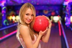 Mädchen steht und umarmt Kugel im Bowlingspielklumpen Lizenzfreies Stockfoto