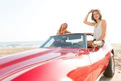 Mädchen am Strand im konvertierbaren Haben des Sportautos lizenzfreies stockfoto