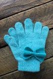 Mädchen-Türkis-Winter-Handschuhe lokalisiert auf einem hölzernen Hintergrund Stockfoto