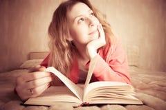 Mädchen träumt, das Buch lesend Stockbild