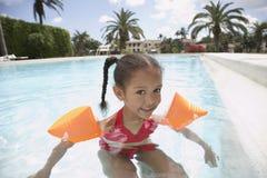 Mädchen-tragende Wasser-Flügel im Swimmingpool stockfoto