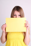 Mädchen tragende yelow Kleidung und Zeigen der leeren Karte Stockfotografie