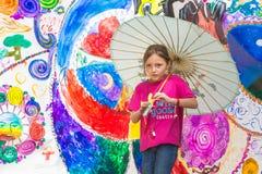 Mädchen-tragender Regenschirm am wilden Gans-Festival Stockfotos