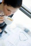 Mädchen trinkendes cofee auf einer transparenten Tabelle Lizenzfreie Stockfotos