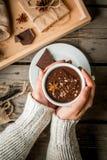 Mädchen trinkt Becher der heißen Schokolade, mit Weihnachtsgeschenk Lizenzfreies Stockbild