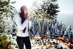 Mädchen trinkt Tee im kalten Winterwald mit Schnee Stockbild
