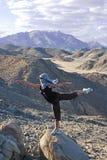 Mädchen tut horizontalen Standplatz auf dem großen Stein Lizenzfreie Stockfotos