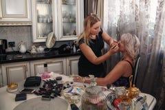 Mädchen tut Make-up den Kunden an Stockbilder