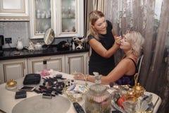 Mädchen tut Make-up den Kunden an Stockfotos
