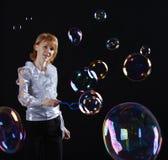 Mädchen tut Seifenluftblasenerscheinen Stockfotos