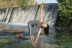 Mädchen tut Yoga im Hintergrund eines Wasserfalls lizenzfreies stockfoto