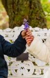 Mädchen u. Junge, die Blumen zusammenhalten Stockfotos