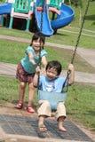 Mädchen u. Junge am Park, der am sonnigen Tag schwingt Stockfotos