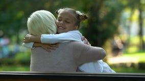 Mädchen umarmt die Oma, die auf Bank, aufrichtige Liebe für die Verwandten sitzt, die Beziehungen vertrauen stock video footage
