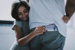 Mädchen-Umarmungen bringen Steals Money From hervor, den Jeans einstecken lizenzfreies stockbild