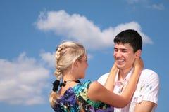 Mädchen umfaßt Kerl für Stutzen auf Himmelhintergrund Lizenzfreie Stockfotografie