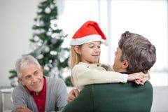 Mädchen-Umfassungsvater During Christmas Lizenzfreie Stockfotos