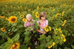 Mädchen umgeben von den Sonnenblumen Lizenzfreies Stockfoto