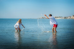 Mädchen und der Kerl spritzten in das Meer Lizenzfreie Stockfotos