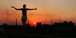 Mädchen und der Sun über einer Fabrik stockbild