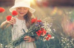 Mädchen und die Mohnblume lizenzfreies stockbild