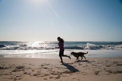 Mädchen und Hund, die auf Strand laufen Lizenzfreie Stockfotos