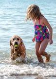Mädchen und Hund, die mit einem Ball am Strand spielen Stockbild