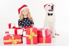 Mädchen und Hund sitzen mit Geschenken Lizenzfreies Stockfoto